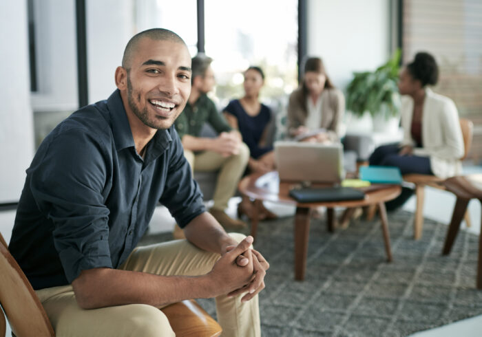 Portrait of a young businessman with his team having a meeting in the background