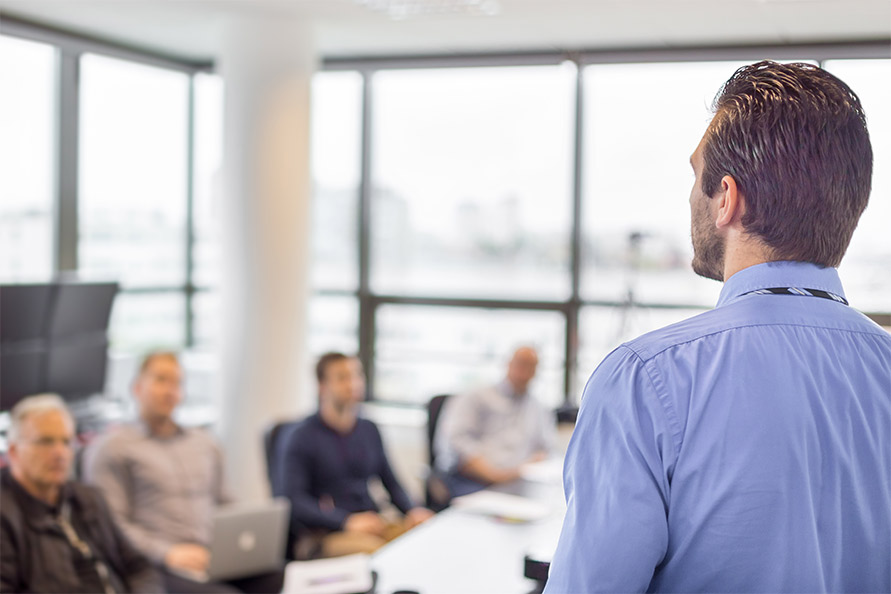Man presenting to a conference room full of other men.