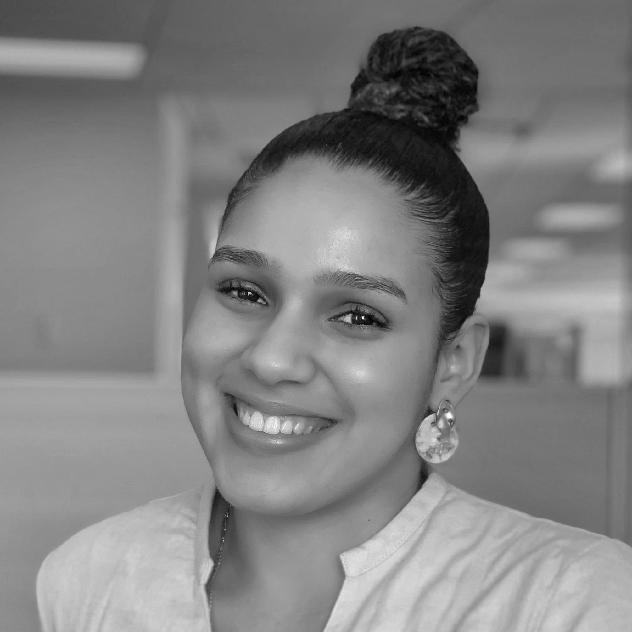 Black and white headshot image of Tahiana Abad, smiling.