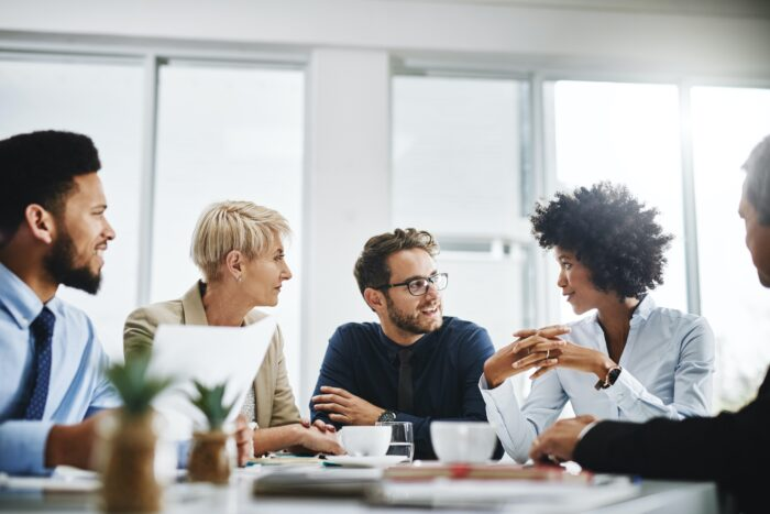 A group of managers engage in lively conversation in a conference room.