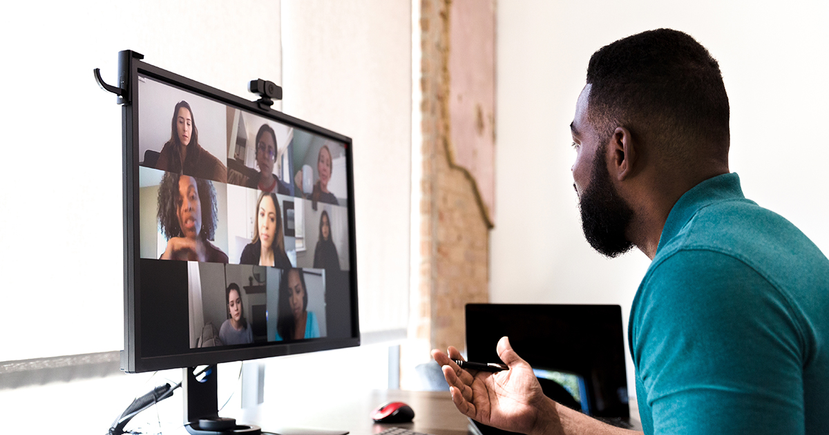 An adult man gestures while talking with a group of colleagues during a virtual staff meeting via video conference.