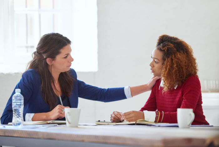 Two coworkers seeting together at a desk, one has a hand on other's shoulder