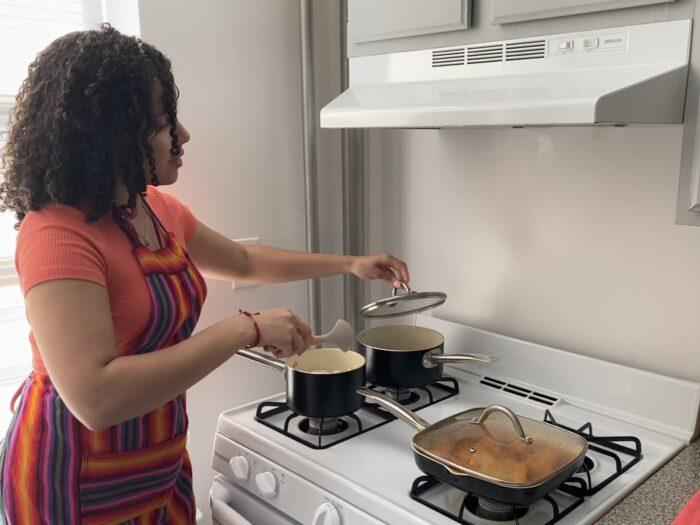 Tahiana Abad cooking white rice, chicken, and guandules.